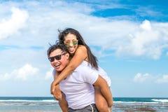 获得亚洲的夫妇在海滩的乐趣热带巴厘岛,印度尼西亚 免版税库存照片