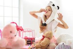 获得俏丽的女孩与玩具熊的乐趣 库存图片