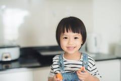 获得儿童的女孩乐趣用红萝卜 与fr的家庭厨房内部 免版税库存图片