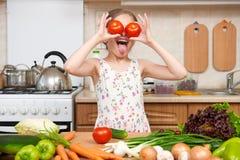 获得儿童的女孩乐趣用蕃茄 家庭厨房内部与 免版税库存照片