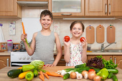 获得儿童的女孩和的男孩乐趣用蕃茄和红萝卜 家庭厨房内部用水果和蔬菜 健康概念的食物 免版税库存图片