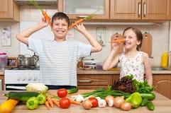 获得儿童的女孩和的男孩乐趣用蕃茄和红萝卜 家庭厨房内部用水果和蔬菜 健康概念的食物 库存图片