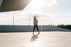 获得全长观点的年轻非洲嬉戏的妇女乐趣 她摇她的在太阳火光的头 库存照片
