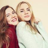 获得冬天的毛线衣的两个年轻女朋友户内乐趣 生活方式 白肤金发的青少年的朋友关闭  免版税库存照片