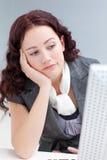 获得办公室年轻人的乏味女实业家 免版税库存图片