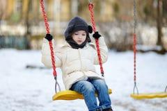 获得可爱的女孩在摇摆的乐趣在冬日 库存图片