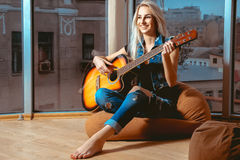 获得可爱的女孩微笑和弹吉他的乐趣 免版税库存图片