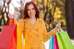 获得可爱的妇女拿着购物袋和乐趣 库存图片