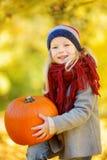 获得可爱的小女孩在一个南瓜补丁的乐趣在美好的秋天天 免版税库存图片