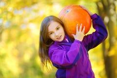 获得可爱的小女孩在一个南瓜补丁的乐趣在美好的秋天天 免版税图库摄影