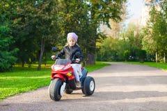 获得可爱的小女孩在她的玩具自行车的乐趣 免版税图库摄影