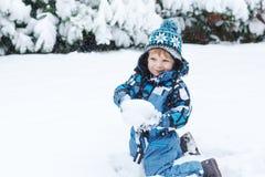 获得可爱的小孩的男孩与雪的乐趣在冬日 免版税库存图片