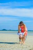 获得可爱的男孩与他的妈妈的乐趣热带海滩的 白色T恤杉、黑暗的长裤和太阳镜 赤足在白色沙子 库存照片