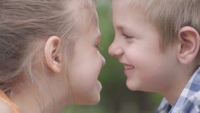 获得可爱的男孩和的女孩的特写镜头面孔坐在公园,设法磨擦他们的鼻子和乐趣 两三愉快 股票录像