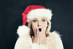 获得圣诞老人的帽子的惊奇的妇女乐趣 背景圣诞节女孩愉快的销售额购物白色 免版税库存照片