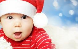 获得圣诞老人的帽子的惊奇的婴孩乐趣,圣诞节 免版税库存图片
