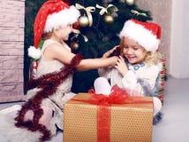 获得圣诞老人的帽子的逗人喜爱的小女孩在圣诞树旁边的乐趣 库存照片