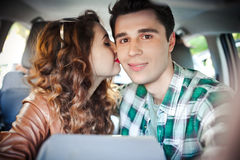 获得在汽车里面的乐趣和做selfie的年轻夫妇 免版税库存照片