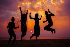 获得在海滩的乐趣和跳跃反对日落的背景的年轻朋友在海的 免版税库存照片