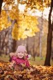 获得在秋天步行的乐趣和坐在叶子的逗人喜爱的微笑的儿童女孩 免版税图库摄影