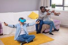获得多种族小组的朋友尝试在3D虚拟现实风镜的乐趣 库存照片