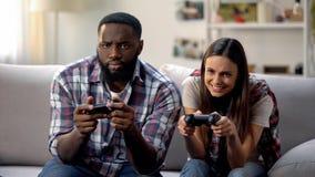 获得好的不同种族的夫妇乐趣,在家打电子游戏,悠闲时间 图库摄影