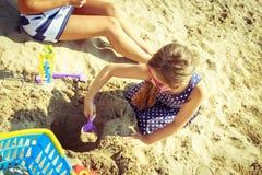 获得家庭的母亲和的女儿在海滩的乐趣 免版税图库摄影