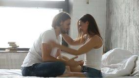 获得富感情的年轻的夫妇乐趣坐床亲吻的拥抱 股票录像