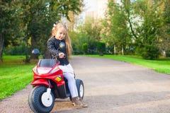 获得小可爱的女孩在她的自行车的乐趣  免版税库存照片