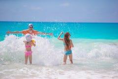获得小女孩和愉快的爸爸在海滨游泳和赛跑的乐趣 免版税库存图片