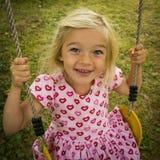 获得小孩白肤金发的女孩在室外的摇摆的乐趣 夏天操场 库存图片