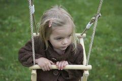 获得小孩白肤金发的女孩在室外的摇摆的乐趣 夏天操场 免版税图库摄影
