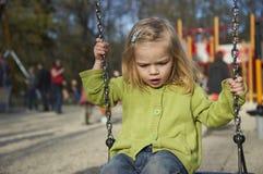 获得小孩白肤金发的女孩在室外的摇摆的乐趣 夏天操场 图库摄影