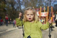 获得小孩白肤金发的女孩在室外的摇摆的乐趣 夏天操场 免版税库存照片