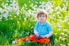 获得小孩的男孩与传统复活节彩蛋狩猎的乐趣 图库摄影