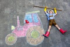 获得小孩的男孩与拖拉机的乐趣用粉笔写图片 免版税图库摄影