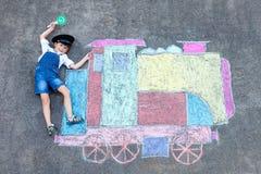 获得小孩的男孩与火车的乐趣用粉笔写图片 库存图片