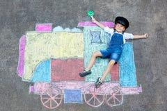 获得小孩的男孩与火车的乐趣用粉笔写图片 免版税库存照片