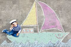 获得小孩的男孩与船图片图画的乐趣与白垩 免版税库存照片