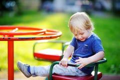 获得小孩的男孩在操场的乐趣 免版税库存照片
