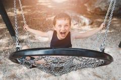 获得小男孩的孩子在儿童摇摆的乐趣 库存图片