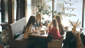 获得小组四的青年人坐在桌上在餐馆和乐趣,当用餐时 股票视频