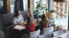 获得小组四的青年人坐在桌上在餐馆和乐趣,当用餐时 股票录像