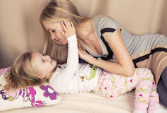 获得小逗人喜爱的女孩与她的妈妈的乐趣 免版税库存照片