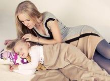 获得小逗人喜爱的女孩与她的妈妈的乐趣 免版税图库摄影