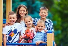获得小组愉快的孩子在操场的乐趣 免版税图库摄影