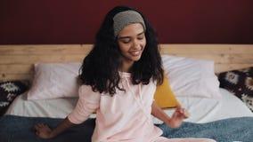 获得年轻可爱的女孩乐趣坐与膝上型计算机的床 她唱歌,跳舞,高兴在喜讯 股票视频