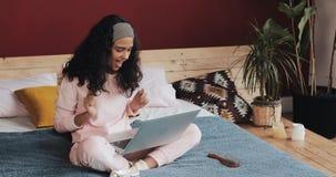 获得年轻可爱的女孩乐趣坐与膝上型计算机的床 她唱歌,跳舞,高兴在喜讯 股票录像