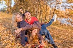 获得年轻微笑的家庭坐秋天草和乐趣 库存图片