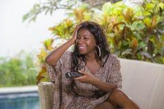 获得年轻愉快和可爱的典雅的黑人非裔美国人的妇女观看的电视藏品的控制器笑的乐趣  库存照片